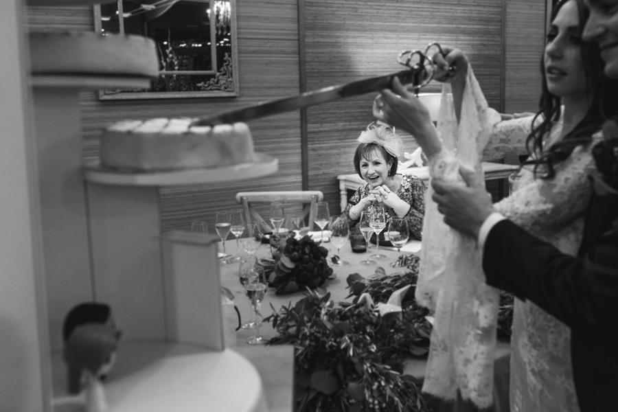 novios cortando tarta mientras madre de la novia observa